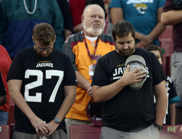 Tampa Bay Buccaneers and Jacksonville Jaguars fans take part in a moment of silence for those affecteed by the shooting at the Jacksonville Landing before an NFL preseason football game Thursday, Aug. 30, 2018, in Tampa, Fla. (AP Photo/Jason Behnken)