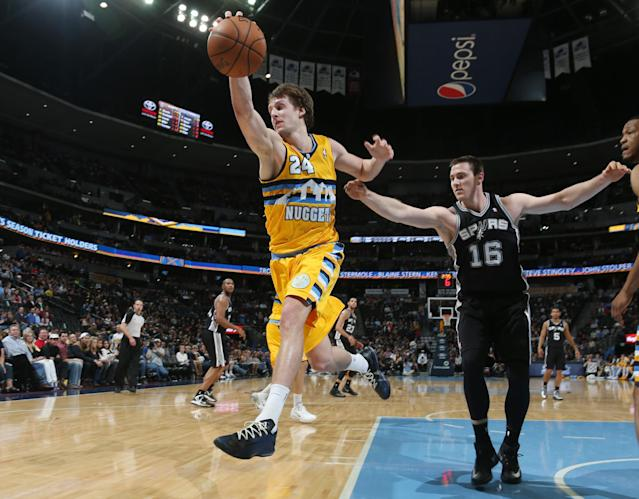 Denver Nuggets forward Jan Vesely, front, of the Czech Republic, reaches to pull in a loose ball as San Antonio Spurs forward Aron Baynes covers in the fourth quarter of the Spurs' 133-102 victory in an NBA basketball game in Denver, Friday, March 28, 2014. (AP Photo/David Zalubowski)