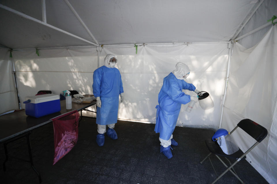 A healthcare worker disinfects a workspace at the end of a day of collecting sample to test for the new coronavirus inside a mobile diagnostic tent, in the Coyoacan district of Mexico City, Friday, Nov. 13, 2020. Mexico City announced Friday it will order bars closed for two weeks after the number of people hospitalized for COVID-19 rose to levels not seen since August. (AP Photo/Eduardo Verdugo)