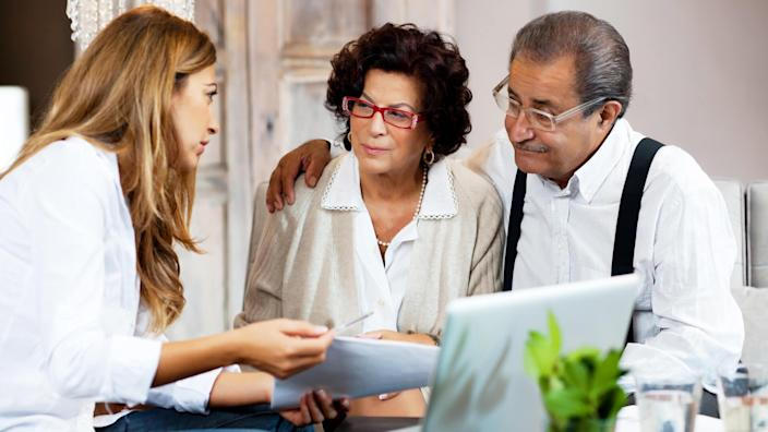 Financial consultant presents bank investments to a senior couple.
