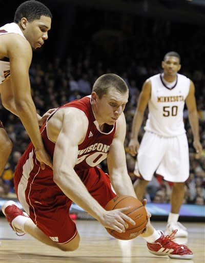 Wisconsin's Jared Berggren (40) recovers a loose ball against Minnesota's Julian Welch, left, during overtime of an NCAA college basketball game Thursday, Feb. 9, 2012, in Minneapolis. Wisconsin defeated Minnesota 68-61. (AP Photo/Genevieve Ross)