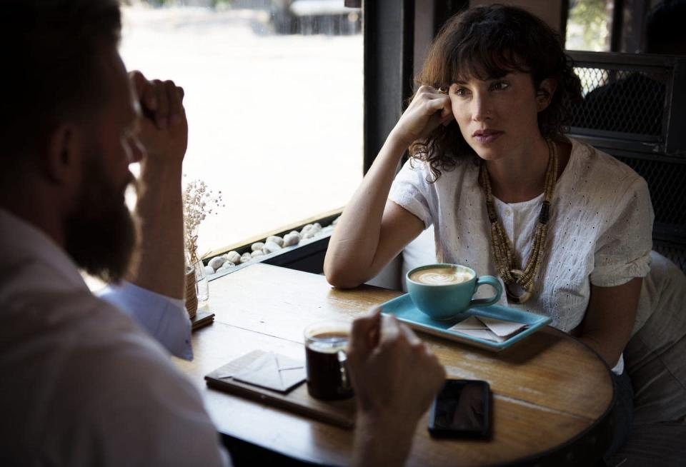 A woman listens to a man speaking in a coffee shop with a latte in front of her.