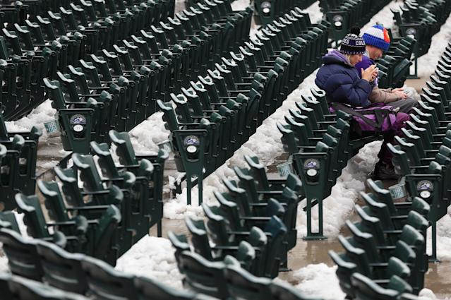DENVER, CO - APRIL 16: Fans sit in the snow covered seating bowl as snow removal delays the start of the double header between the New York Mets and the Colorado Rockies at Coors Field on April 16, 2013 in Denver, Colorado. All uniformed team members are wearing jersey number 42 in honor of Jackie Robinson Day. (Photo by Doug Pensinger/Getty Images)