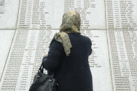 Djulija Jusic who lost her two sons and the 33 relatives in Srebrenica massacre, looks at names at the memorial cemetery in Potocari near Srebrenica, Bosnia, Friday, May 28, 2021. U.N. judges on Tuesday, June 8 deliver their final ruling on the conviction of former Bosnian Serb army chief Radko Mladic on charges of genocide, war crimes and crimes against humanity during Bosnia's 1992-95 ethnic carnage. Nearly three decades after the end of Europe's worst conflict since World War II that killed more than 100,000 people, a U.N. court is set to close the case of the Bosnian War's most notorious figure. (AP Photo/Eldar Emric)