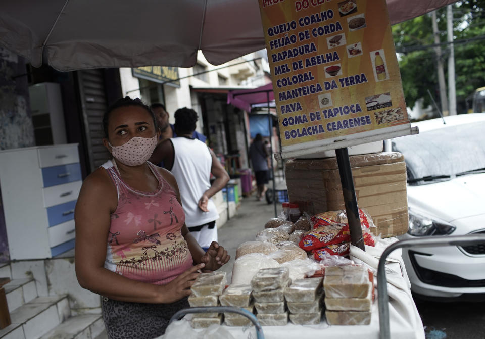 A street vendor wearing a mask amid COVID-19 sells cheese, beans, and sweets in Rio de Janeiro, Brazil, Friday, Oct. 9, 2020. Many people in Brazil are struggling to cope with less pandemic aid from the government and jumping food prices, with millions expected to slip back into poverty. (AP Photo/Silvia Izquierdo)