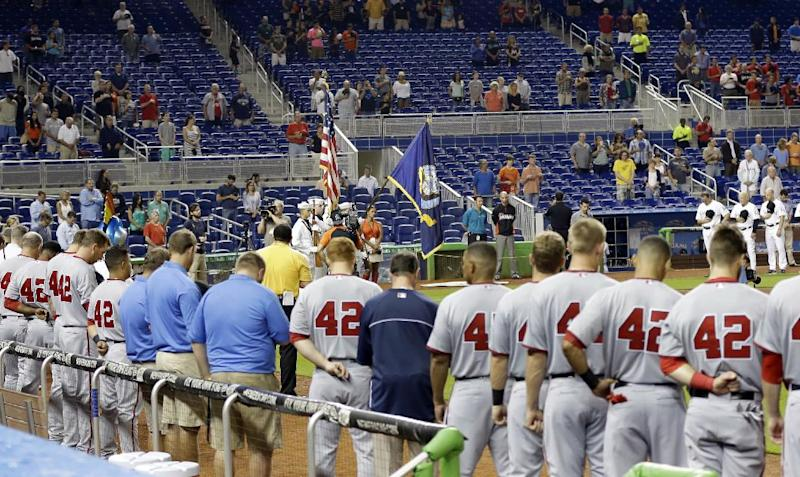 Baseball players and fans stand during a moment of silence for the victims of explosions at the Boston Marathon, before the start of a baseball game between the Miami Marlins and the Washington Nationals, Monday, April 15, 2013 in Miami. The players were wearing Jackie Robinson's No. 42. (AP Photo/Wilfredo Lee)