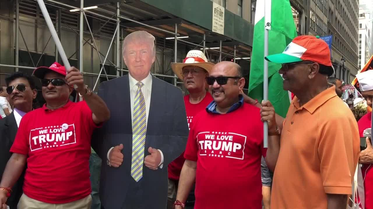 Participants of the India Day Parade proudly express their support for President Trump by wearing Trump T-shirts and taking pictures with a cardboard cut-out version of the President.   Footage shows the Trump supporters waving India's national flag while posing for photographs.   The New York India Day Parade travels through the main island of Manhattan and is the largest outside of India which marks India's independence.  The theme this year was to support valour and sacrifice of Americas armed forces   The theme this year was to support valour and sacrifice of America's armed forces.  The parade displayed many performances by young INdian-Americans, artwork and marching bands. This years Grand MArshall was the well-known Indian actor and entrepreneur Suniel Shetty