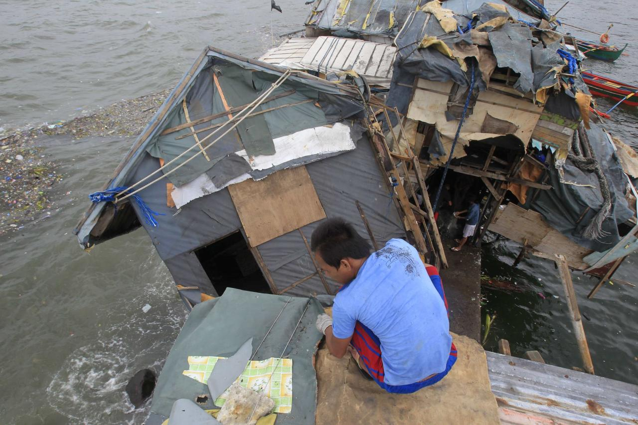 A man fixes the roof of his house beside another damaged house after strong winds brought by Typhoon Rammasun (locally name Typhoon Glenda) battered the coastal area of Baseco compound, metro Manila July 17, 2014. The Philippines set to work clearing debris, reconnecting power and rebuilding flattened houses on Thursday after a typhoon swept across the country killing 38 people, with at least eight missing, rescue officials said. Typhoon Rammasun, the strongest storm to hit the Philippines this year, was heading towards China after cutting a path across the main island of Luzon, shutting down the capital and knocking down trees and power lines, causing widespread blackouts. REUTERS/Romeo Ranoco(PHILIPPINES - Tags: ENVIRONMENT DISASTER)