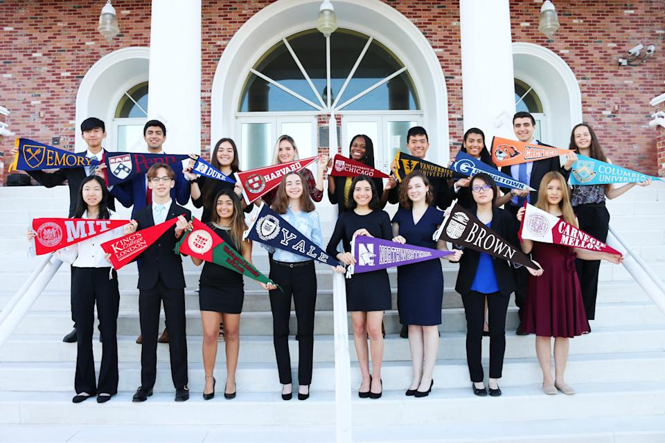 Students hold up college pennants.