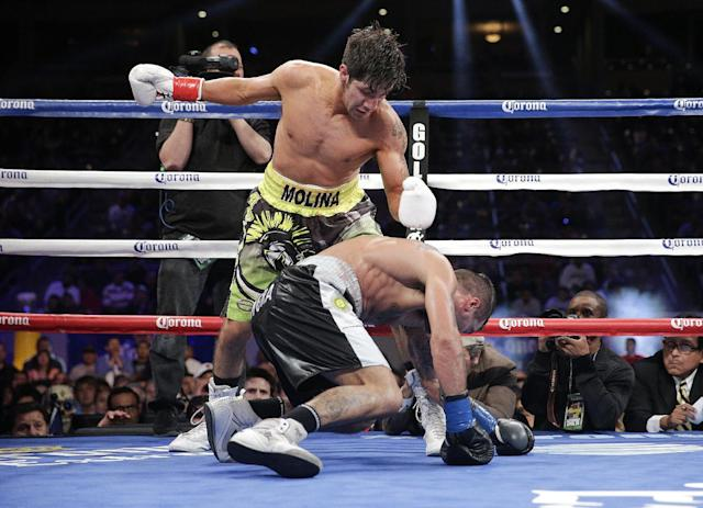 John Molina, top, knocks down Lucas Matthysse, of Argentina, during the fifth round of a boxing match Saturday, April 26, 2014, in Carson, Calif. (AP Photo/Jae C. Hong)