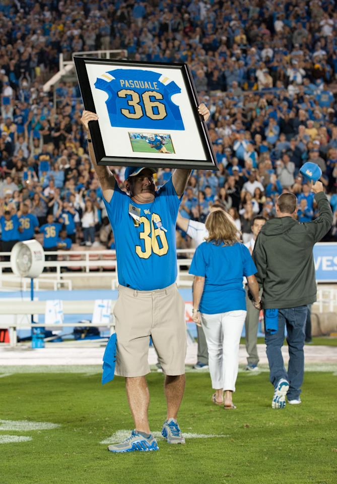 PASADENA, CA - SEPTEMBER 21: (L-R) Mel Pasquale holds up the framed jersey of his son Nick Pasquale #36 as the UCLA Bruins honor his memory during the first quarter break against the New Mexico State Aggies at the Rose Bowl on September 21, 2013 in Pasadena, California. (Photo by Don Liebig-Pool/Getty Images)