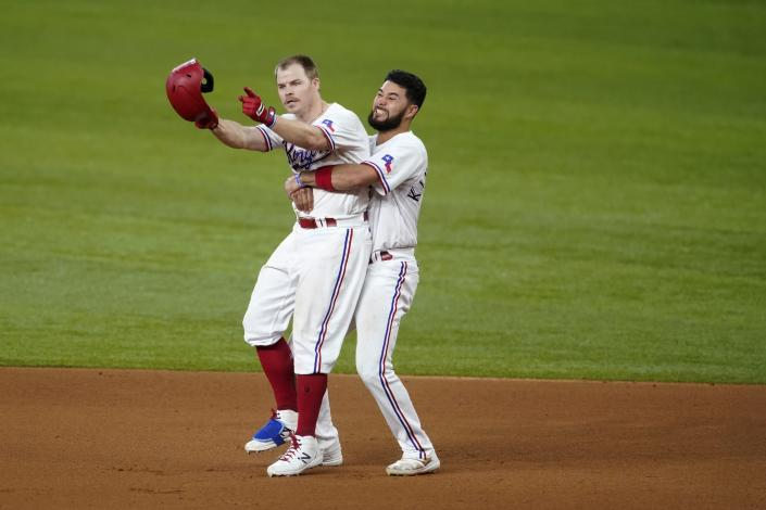 Texas Rangers' Brock Holt, left, and Isiah Kiner-Falefa, right, celebrate Holt's walk-off single in the 11th inning of the team's baseball game against the San Francisco Giants in Arlington, Texas, Wednesday, June 9, 2021. (AP Photo/Tony Gutierrez)