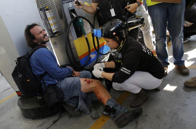 Associated Press photographer Rodrigo Abd who was injured by riot police, is assisted while sitting in a petrol station during a protest against the 2014 World Cup, in Sao Paulo June 12, 2014. REUTERS/Nacho Doce (BRAZIL - Tags: SPORT SOCCER WORLD CUP POLITICS CIVIL UNREST MEDIA)