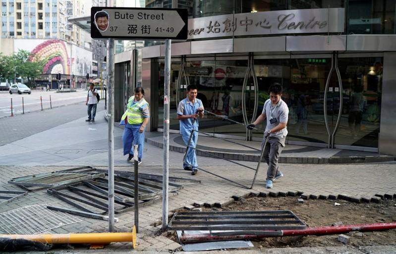 Municipality workers clean the debris of Sunday's anti-government protest in Hong Kong