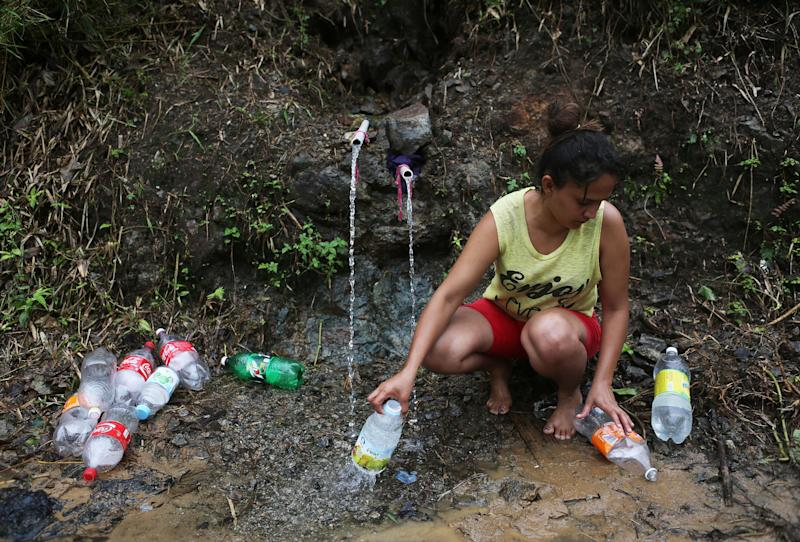 Yanira Rios collects spring water for use in her house last week in Utuado, Puerto Rico. Most of the municipality has been without running water or electricity since Hurricane Maria hit the island on Sept. 20. (Mario Tama via Getty Images)
