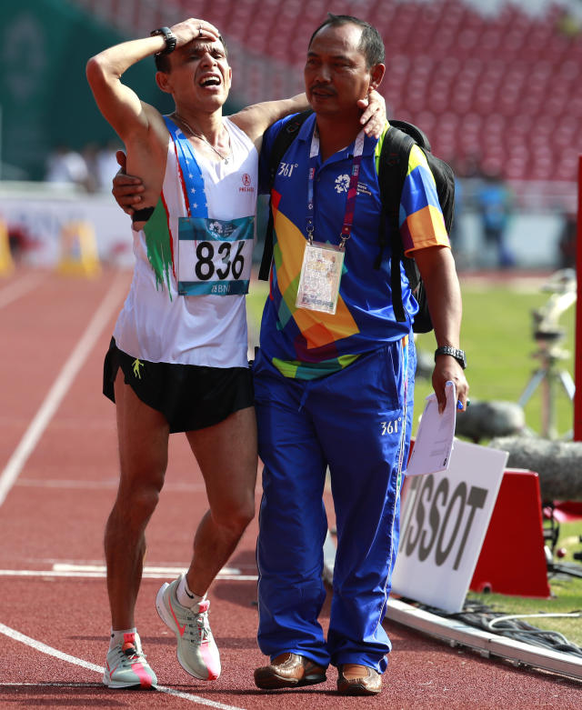 Uzbekistan's Andrey Petrov is assisted from the track after completing the men's marathon at the 18th Asian Games in Jakarta, Indonesia, Saturday, Aug. 25, 2018. (AP Photo/Bernat Armangue)