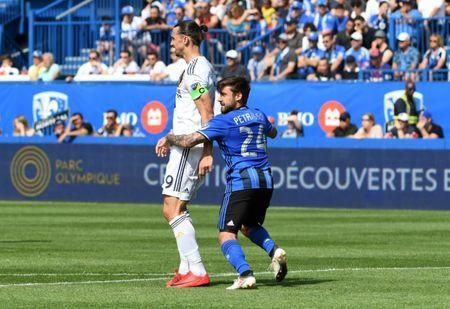 May 21, 2018; Montreal, Quebec, CAN; Montreal Impact defender Michael Petrasso (24) and Los Angeles Galaxy forward Zlatan Ibrahimovic (9) during the first half at Stade Saputo. Mandatory Credit: Eric Bolte-USA TODAY Sports