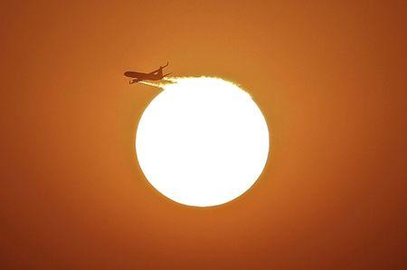 An aircraft files near the setting sun in New Delhi