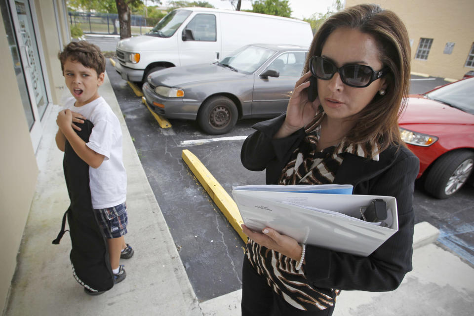 Businesswoman Irela Bague multitasks as she drops her son, Alberto, at his father's office in Miami. (Photo: Al Diaz/Miami Herald/MCT via Getty Images)