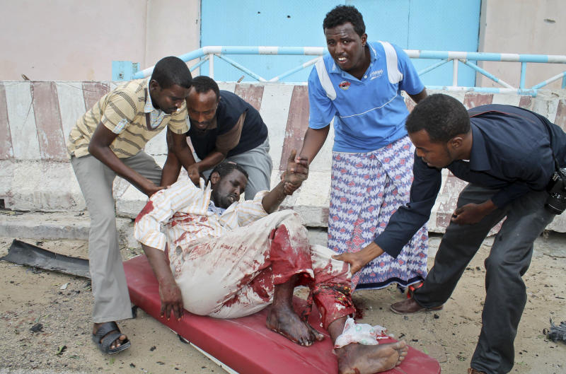Somalis carry a man who was wounded during an attack on the U.N. compound in Mogadishu, Somalia Wednesday, June 19, 2013. Al-Qaida-linked militants detonated multiple bomb blasts and engaged in ongoing battles with security forces in an attempt to breach the main U.N. compound in Mogadishu, officials said Wednesday. (AP Photo/Farah Abdi Warsameh)
