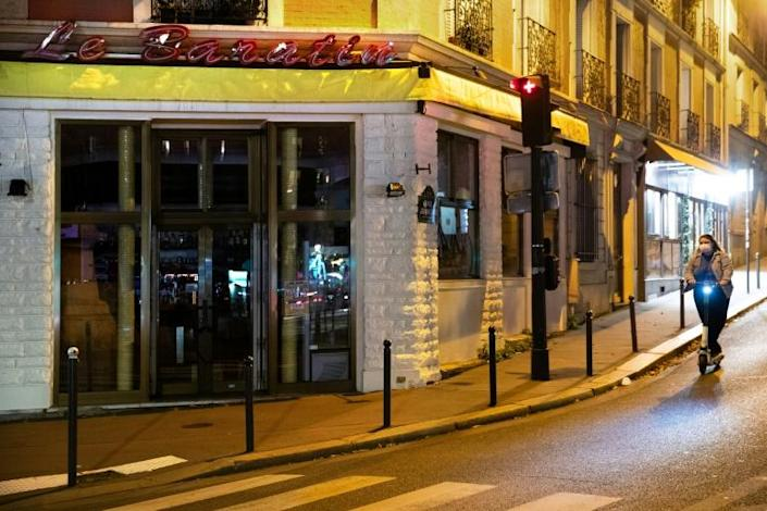 A woman walks by a closed restaurant in France during a second lockdown
