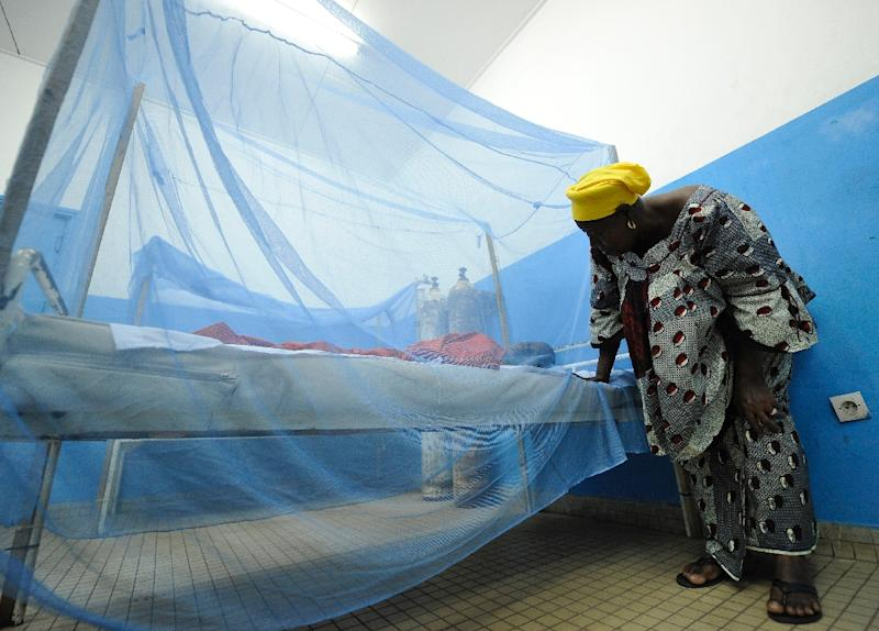 A woman looks at her sick child laying under a mosquito net in a hospital on April 24, 2015 in Abidjan (AFP Photo/Sia Kambou)