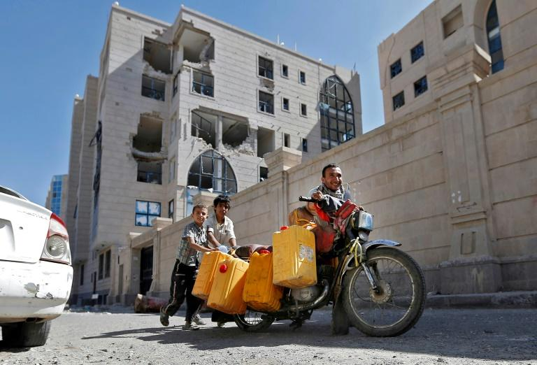 Yemenis push a motorcycle loaded with jerrycans down a street leading to the residence of Yemen's late ex-president Ali Abdullah Saleh in the capital Sanaa on December 6, 2017