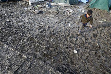 A young migrant runs in a muddy field at a camp of makeshift shelters for migrants and asylum-seekers from Iraq, Kurdistan, Iran and Syria, called the Grande Synthe jungle, near Dunkirk, France, January 25, 2016.   REUTERS/Yves Herman