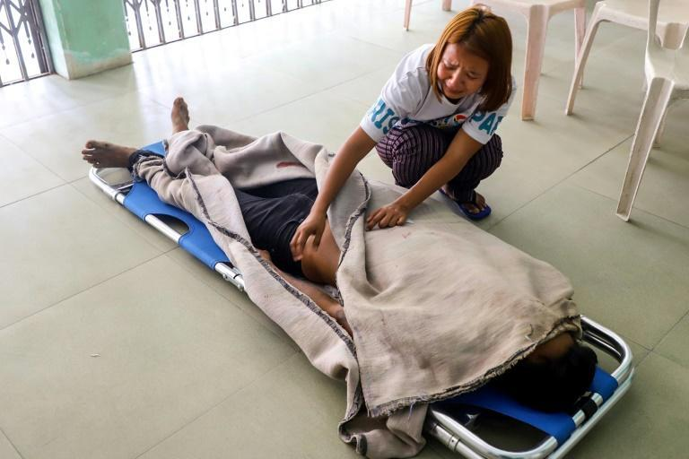 The sister of Saw Pyae Naing, who was killed during a demonstration on Saturday, grieves over his body at a makeshift medical centre in Mandalay