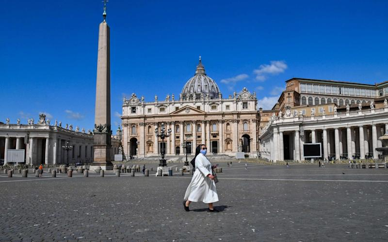 A nun walks across St. Peter's Square past St. Peter's Basilica - AFP
