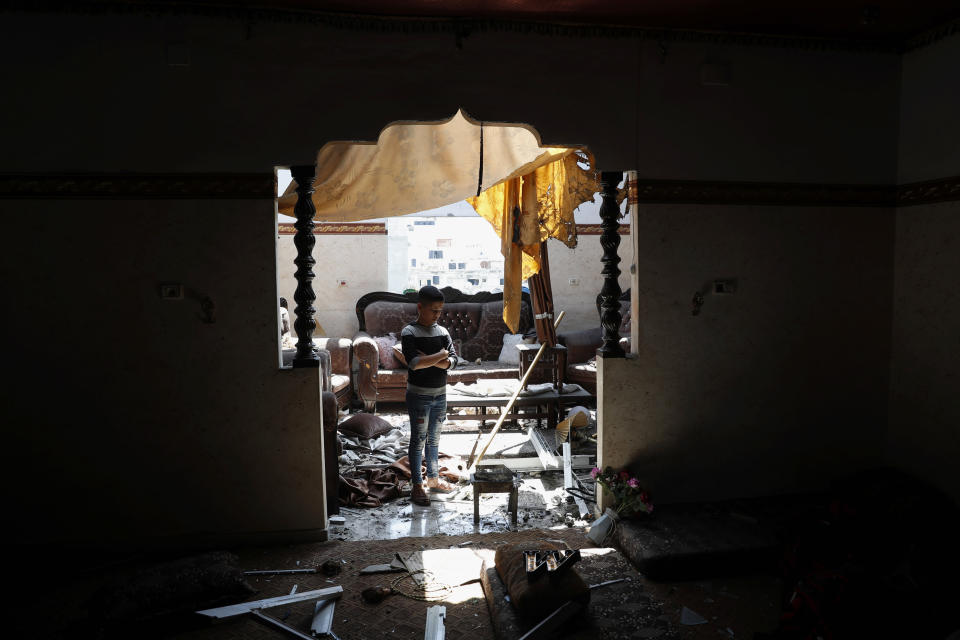 A child looks at the damaged room of his family apartment after by Israeli airstrikes near a residential building, in Beit Lahiya, Gaza Strip, Thursday, May 20, 2021. (AP Photo/Adel Hana)