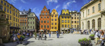 Stockholm, Sweden - July 9, 2016: Crowds of tourists and locals enjoying the summer sunshine beneath the colourful townhouses and quaint restaurants of historic Stortorget, Great Square, the iconic landmark plaza on Gamla Stan in the heart of Stockholm, Sweden's vibrant capital city. Composite panoramic image created from six contemporaneous sequential photographs.