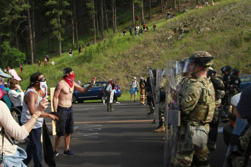 Protesters clash with a line of law enforcement officers in Keystone, S.D., on the road leading to Mount Rushmore ahead of President Donald Trump's visit to the memorial on Friday, July 3, 2020. (AP Photo/Stephen Groves)