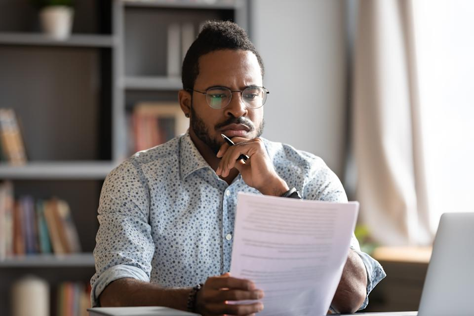 African student guy sit at desk hold papers tasks having difficulties with test, company lawyer read contract terms and detail feels discontented, received bad news from bank unpleasant letter concept