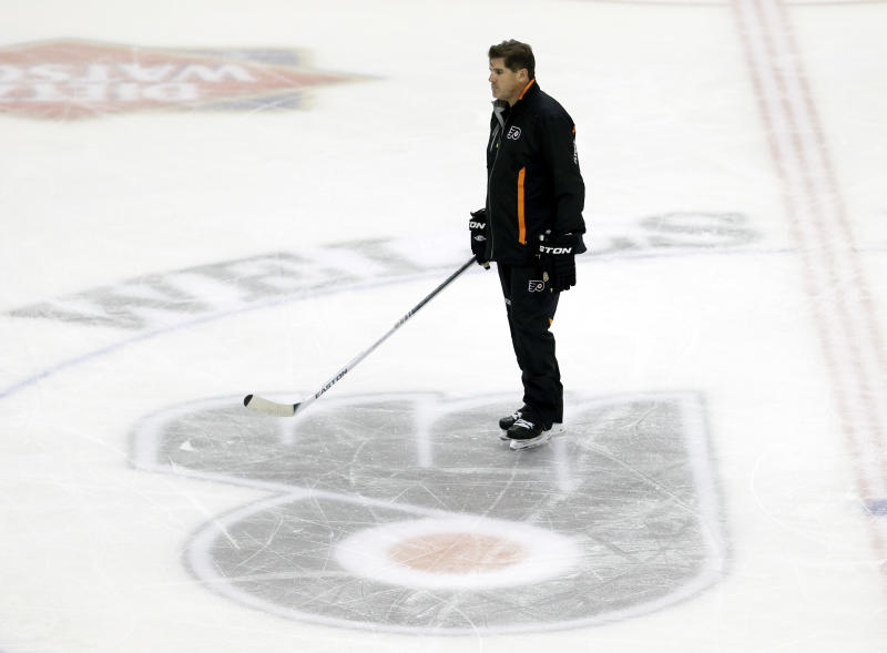 FILE - In this Sept. 12, 2013 file photo, Philadelphia Flyers head coach Peter Laviolette skates over a Flyers logo during training camp in Philadelphia. The Flyers fired coach Laviolette, a person familiar with the decision told The Associated Press on Monday, Oct. 7, 2013.(AP Photo/Matt Rourke, File)