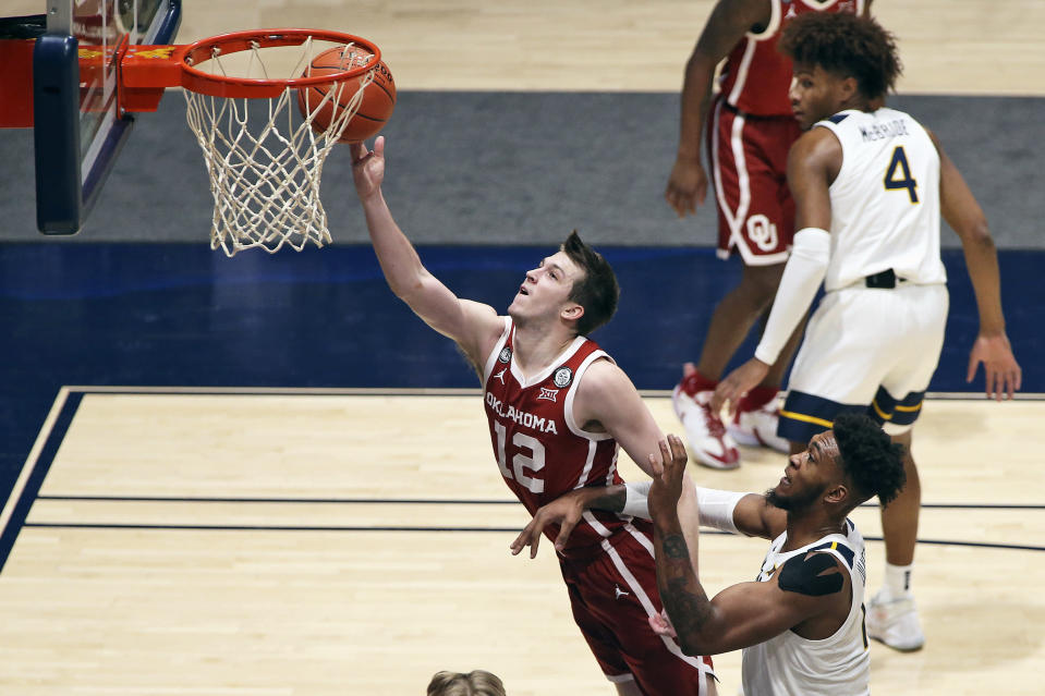 Oklahoma guard Austin Reaves (12) shoots past West Virginia forward Derek Culver (1) during the second half of an NCAA college basketball game Saturday, Feb. 13, 2021, in Morgantown, W.Va. (AP Photo/Kathleen Batten)