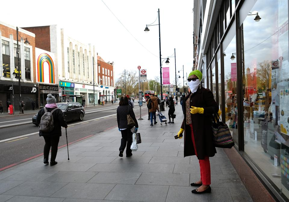 A woman wearing a scarf and plastic gloves as a precautionary measure for Covid-19, waits for a bus in the high street in Brixton, south London, as the UK continues in lockdown to help curb the spread of the coronavirus. Picture date: Monday April 6, 2020.