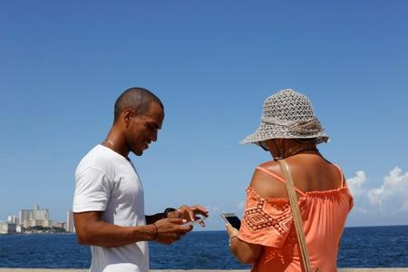 Jason Sanchez makes a transaction with cryptocurrency using the startup Fusyona at the seafront Malecon in Havana