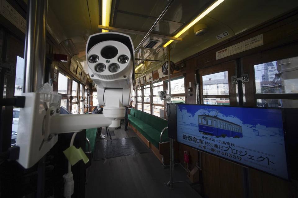 For live-streaming of running on a street, some TV cameras are set inside a tram which survived the Hiroshima atomic bombing, at a train maintenance facility in Hiroshima, western Japan, Monday, Aug. 3, 2020. It has been restored and repainted its original colors, will run on the street on Aug. 6 to commemorate the day of the U.S. first atomic bombing in the city. (AP Photo/Eugene Hoshiko)
