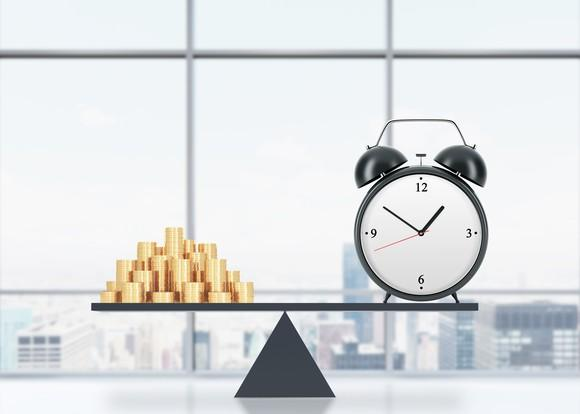 Pile of gold coins opposite a clock on a balance beam