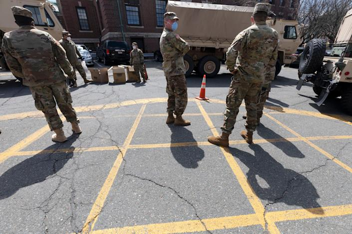 Massachusetts National Guard soldiers help with logistics in this Friday, April 17, 2020 file photo, at a food distribution site outside City Hall, in Chelsea, Mass. Mass. Gov. Charlie Baker on Monday, Sept. 13, 2021, activated the state's National Guard to help with busing students to school as districts across the country struggle to hire enough drivers.