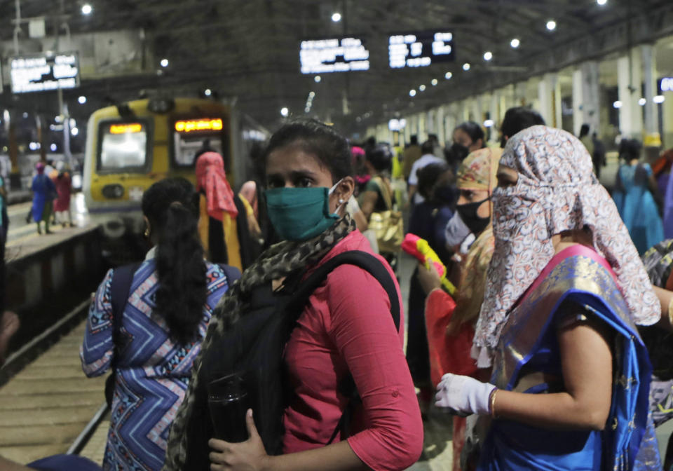 Women passengers wait for a local train in Mumbai, India, Wednesday, Oct. 21, 2020. Indian railways has permitted women passengers to travel in local trains during non-peak hours beginning Wednesday, which otherwise has been running only for essential services. (AP Photo/Rajanish Kakade)