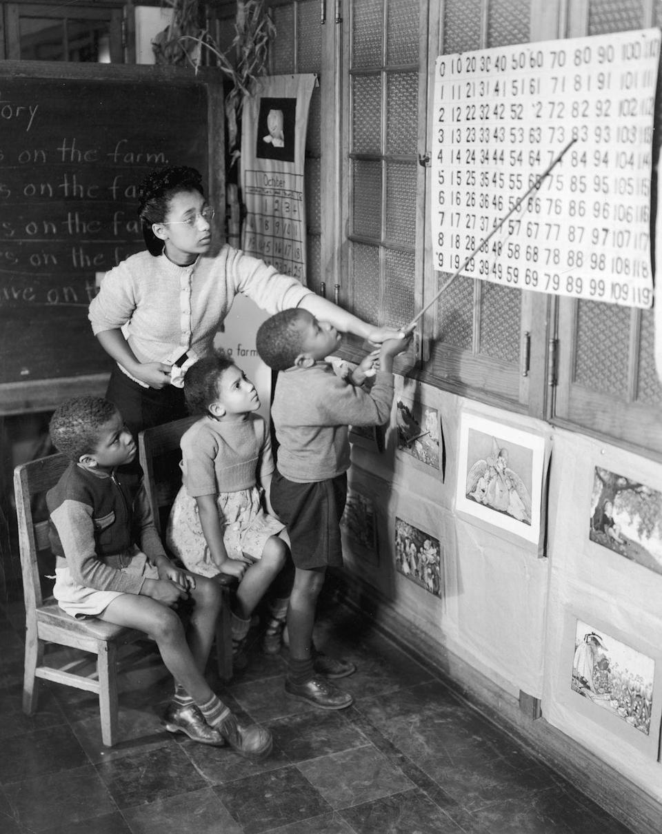 <p>A teacher in Hampton, Virginia uses a pointer to help her young students study arithmetic. </p>