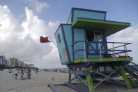 A red flag flies from a lifeguard station indicating high surf, Friday, July 31, 2020, in Miami Beach, Fla. Forecasters declared a hurricane warning for parts of the Florida coast Friday as Hurricane Isaias drenched the Bahamas on track for the U.S. East Coast. (AP Photo/Lynne Sladky)