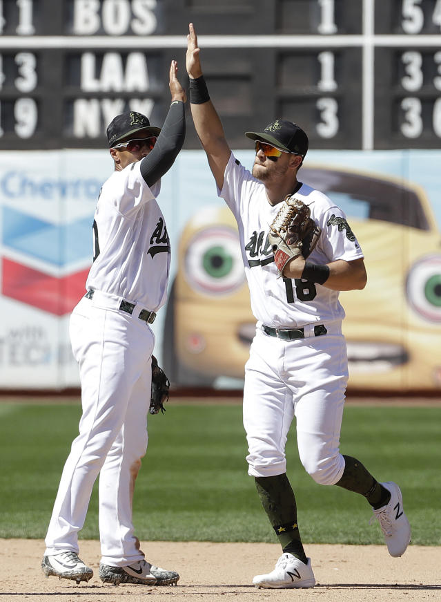 Oakland Athletics shortstop Marcus Semien, left celebrates with Chad Pinder after the Athletics beat the Arizona Diamondbacks in a baseball game in Oakland, Calif., Sunday, May 27, 2018. The Athletics won 2-1. (AP Photo/Jeff Chiu)