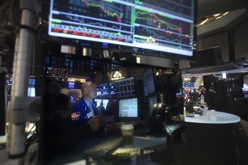 Trader is reflected in a screen as he works on the floor of the NYSE in New York