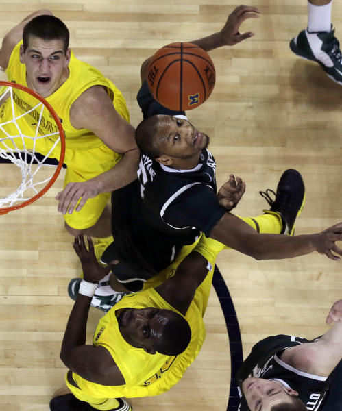 Michigan State forward Adreian Payne, center, Michigan forward Mitch McGary, top, and guard Tim Hardaway Jr. battle for the rebound during the second half of an NCAA college basketball game in Ann Arbor, Mich., Sunday, March 3, 2013. (AP Photo/Carlos Osorio)