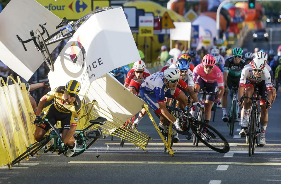 Dutch cyclist Dylan Groenewegen crashes to the ground as a bicycle is flying overhead in a major collision on the final stretch of the opening stage of the Tour de Pologne race in Katowice, Poland, Wednesday, Aug. 5, 2020. The crash began with Groenewegen colliding with another Dutchman sprinting for the win, Fabio Jakobsen, who was hospitalized in serious condition and put into an induced coma. Jakobsen was declared the winner of the opening stage and Groenewegen was disqualified. (AP Photo/Tomasz Markowski)