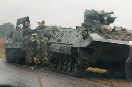 Soldiers stand beside military vehicles just outside Harare, Zimbabwe, November 14, 2017. REUTERS/Philimon Bulawayo