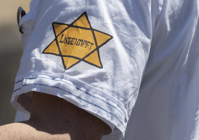 """A man is seen wearing a yellow star of David with the the word """"Unvaccinated"""" on his sleeve at a demonstration against coronavirus restrictions in Frankfurt, Germany on May 16, 2020. Some protesters in Germany, who've compared the current government's coronavirus restrictions to Nazi policies, have begun displaying such patches or arm bands, like the ones European Jews were forced to wear during the Holocaust. (Boris Roessler/picture alliance via Getty Images)"""